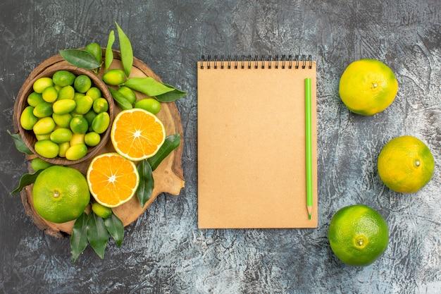 Vista superior de longe frutas cítricas laranjas tangerinas no quadro de lápis de caderno