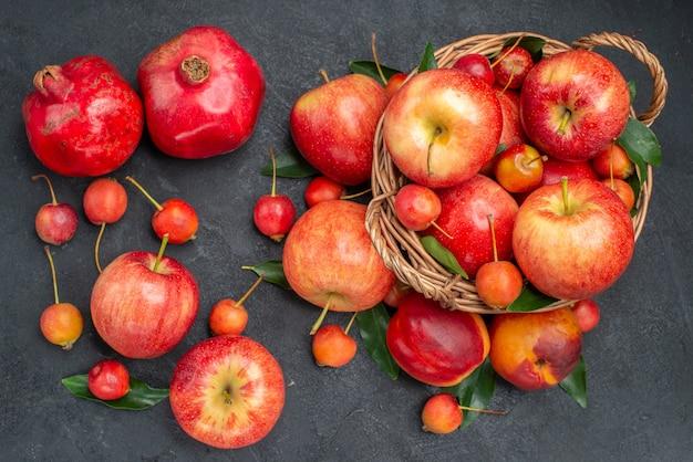 Vista superior de longe frutas maçãs cerejas na cesta nectarina romãs