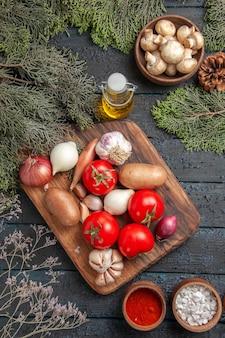 Vista superior de longe, legumes e ramos de tábua de cortar com legumes entre especiarias coloridas e tigela de óleo de cogumelos brancos e ramos de abeto com cones