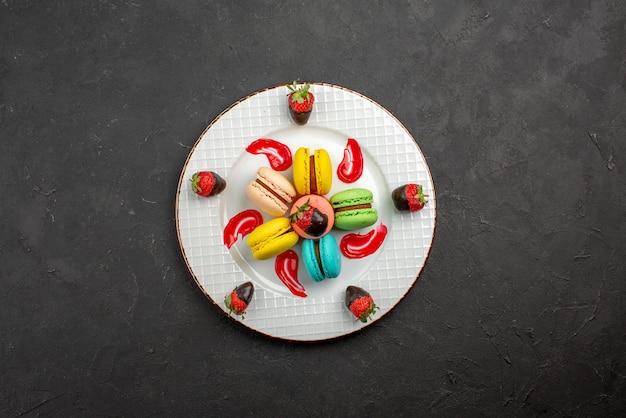 Vista superior de longe macaroon francês macaroon francês com morangos cobertos de chocolate no centro da mesa escura