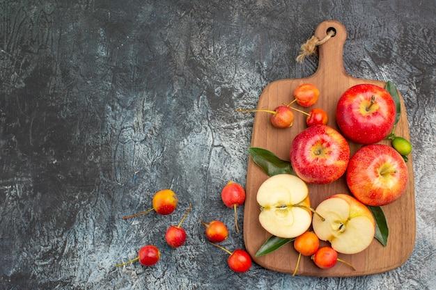 Vista superior de longe, maçãs, apetitosas maçãs vermelhas, cerejas na tábua