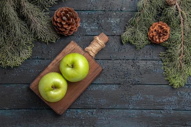 Vista superior de longe maçãs entre cones duas maçãs verdes em uma tábua entre galhos de árvores com cones