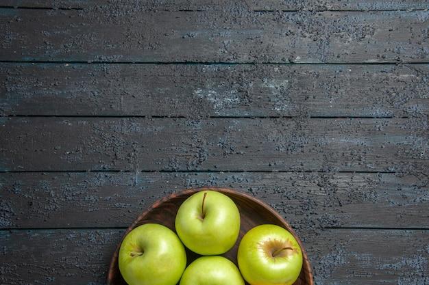 Vista superior de longe maçãs verdes sete maçãs verdes em uma tigela na superfície escura