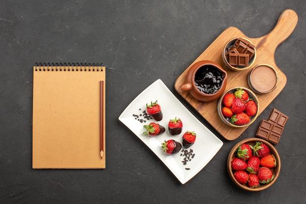 Vista superior de longe, morangos com chocolate, morangos com cobertura de chocolate, chocolate e tabuleiro de cozinha com creme de chocolate e morangos ao lado do caderno e do lápis