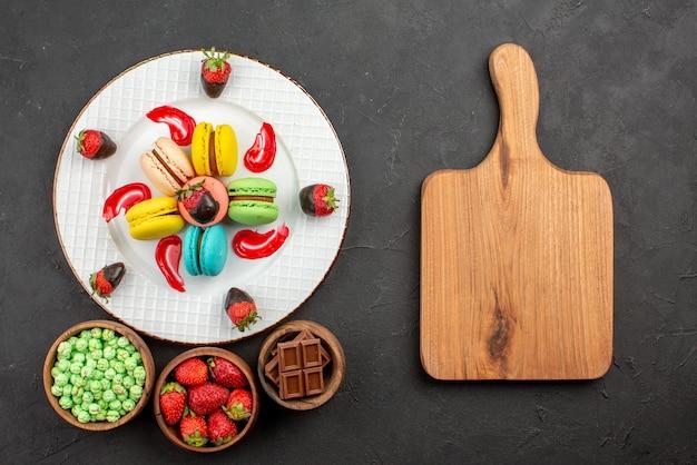 Vista superior de longe, morangos e macaroons prato de apetitosos morangos molho de macarons franceses ao lado da tábua de cortar e tigelas de doces na mesa escura
