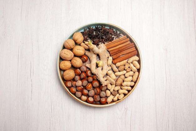 Vista superior de longe, nozes e nozes com canela, avelãs, paus de canela, amendoim e anis estrelado na mesa