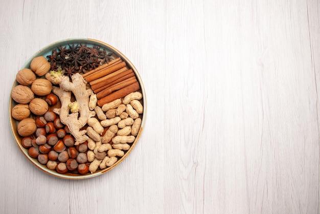 Vista superior de longe, nozes e nozes com canela, avelãs, paus de canela, amendoim e anis estrelado no lado esquerdo da mesa