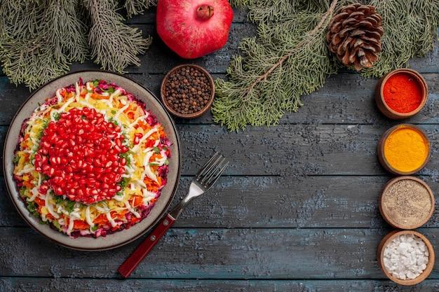 Vista superior de longe o prato e o prato de galhos de árvores com sementes de romãs ao lado das tigelas de especiarias, garfo de romã e cones de galhos de árvores