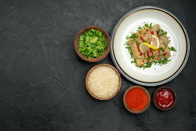Vista superior de longe prato com molho de repolho recheado com ervas de limão e molho na chapa branca e especiarias ervas de arroz e molho em tigelas no lado direito da mesa escura