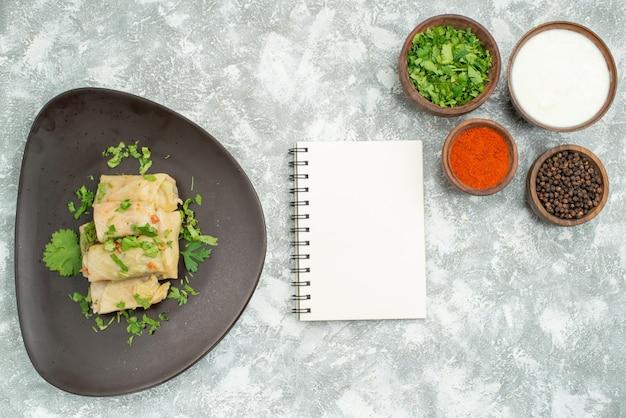 Vista superior de longe prato com prato de ervas de repolho recheado ao lado de caderno branco e tigelas com ervas de creme azedo de pimenta preta e especiarias no lado esquerdo e direito da mesa