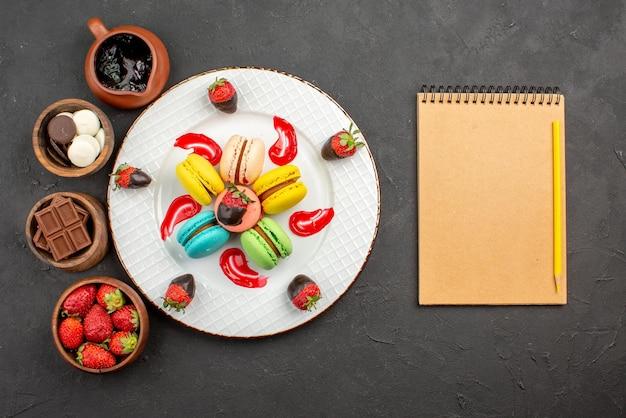 Vista superior de longe prato doce prato de macaroon e quatro tigelas de doces de chocolate, morangos e creme de chocolate ao lado do caderno e lápis no fundo escuro