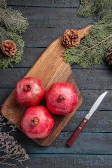 Vista superior de longe romãs e romãs em forma de faca na mesa da cozinha ao lado da faca e dos ramos de espeto com cones