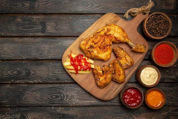 Vista superior de longe taças de coxa e asas de frango com molhos coloridos e temperos, coxa e asas de frango e batatas fritas na tábua de corte