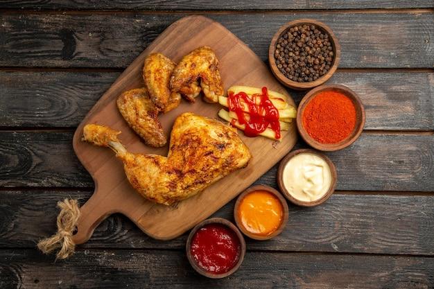 Vista superior de longe tigelas de frango com temperos e molhos ao lado do frango com batatas fritas e ketchup na tábua de corte