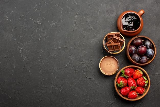 Vista superior de longe, tigelas de molho de chocolate com morangos e molho de chocolate no lado da mesa