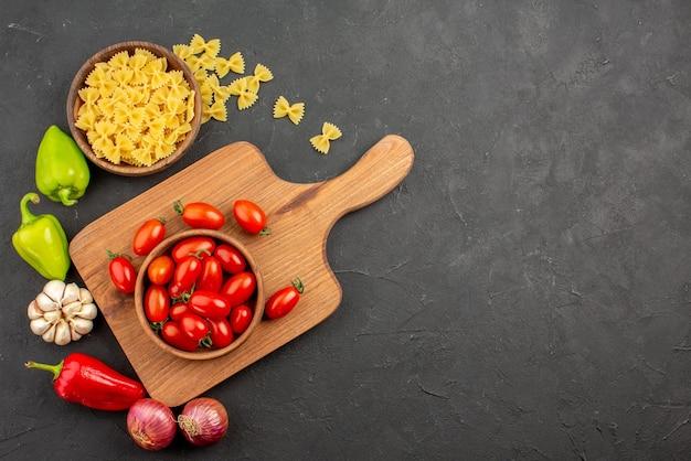 Vista superior de longe tomate no quadro macarrão pimentão alho cebola e tomate maduro em uma tigela na placa de madeira sobre a mesa