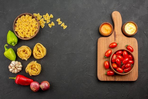 Vista superior de longe tomates e especiarias diferentes tipos de macarrão pimentão cebola alho no lado esquerdo e a tigela de tomates na placa de madeira e molhos no lado direito da mesa