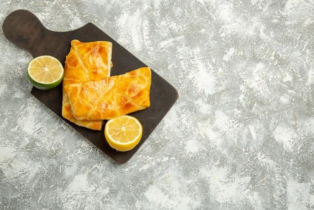 Vista superior de longe tortas a bordo de duas tortas de limão e limão na placa da cozinha no lado esquerdo da mesa