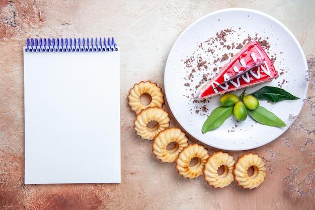 Vista superior de longe um prato de bolo apetitoso caderno branco de seis biscoitos