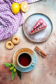 Vista superior de longe uma xícara de chá uma xícara de chá biscoitos canela limão prato de bolo toalha de mesa
