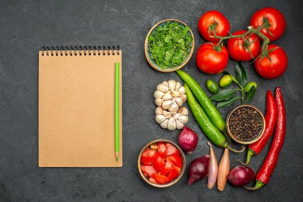 Vista superior de longe vegetais vegetais ervas especiarias cebola pimenta picante caderno lápis