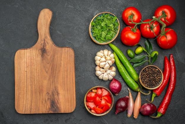 Vista superior de longe vegetais vegetais ervas especiarias cebola pimenta pimenta a tábua de cortar