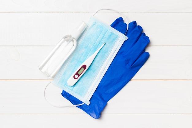Vista superior de luvas cirúrgicas, um frasco de desinfetante para as mãos e termômetro