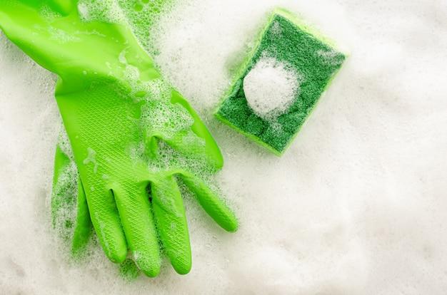 Vista superior de luvas de proteção verdes e esponja na parede com sabão. conceito de trabalho doméstico. copie o espaço, vista superior