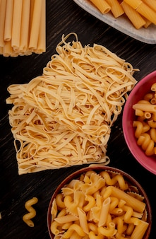 Vista superior de macaronis como tagliatelle bucatini fusilli e outros na madeira