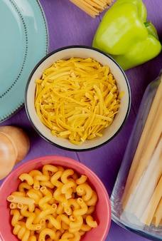 Vista superior de macaronis como tagliatelle cavatappi bucatini com pimenta e prato na superfície roxa