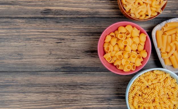 Vista superior de macaronis diferentes como rotini ziti pipe-rigate e outros na madeira com espaço de cópia