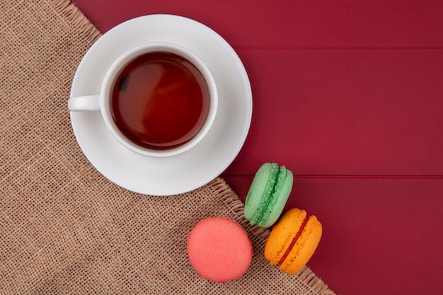 Vista superior de macarons coloridos com uma xícara de chá em um guardanapo bege sobre uma superfície vermelha