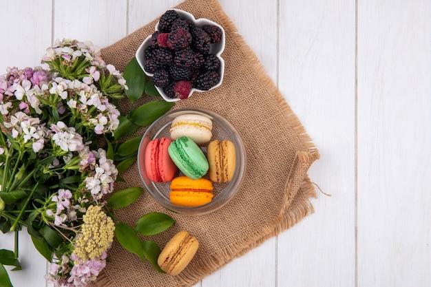 Vista superior de macarons coloridos em uma jarra com flores e amoras em uma superfície branca