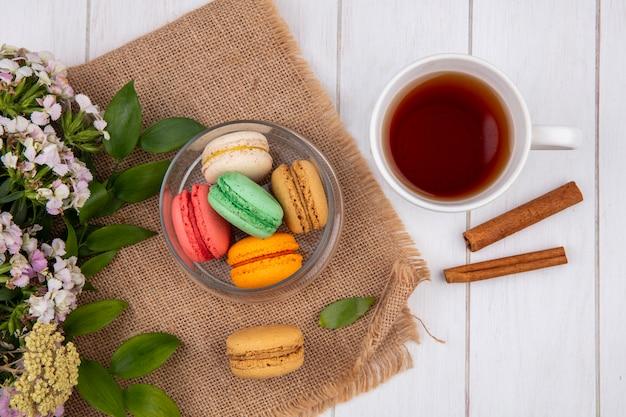 Vista superior de macarons coloridos em uma jarra com flores e uma xícara de chá com canela em uma superfície branca