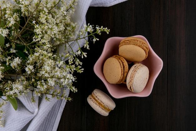 Vista superior de macarons em um pires com flores em uma toalha branca em uma superfície de madeira