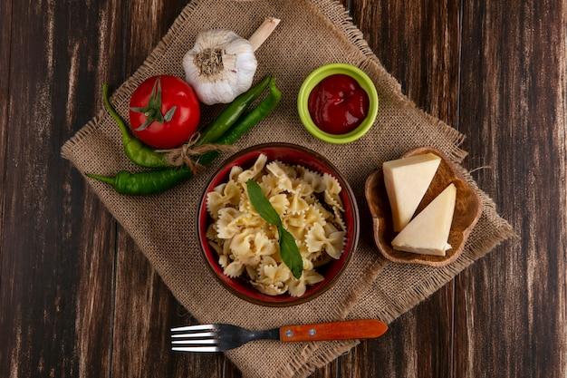 Vista superior de macarrão cozido em uma tigela com um garfo tomate pimenta pimenta alho e queijo em um guardanapo bege