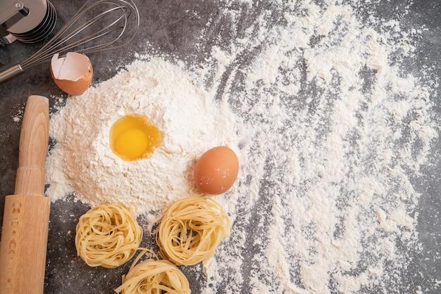 Vista superior de macarrão cru com ovo na farinha e cópia-espaço