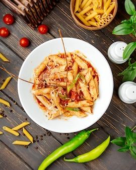 Vista superior de macarrão penne com molho de tomate e pimentão