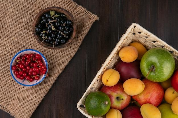 Vista superior de maçãs coloridas com damascos e pêssegos com limão em uma cesta com groselhas vermelhas e pretas em uma superfície de madeira