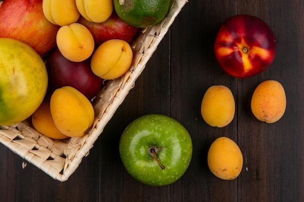 Vista superior de maçãs coloridas com damascos e pêssegos com limão em uma cesta