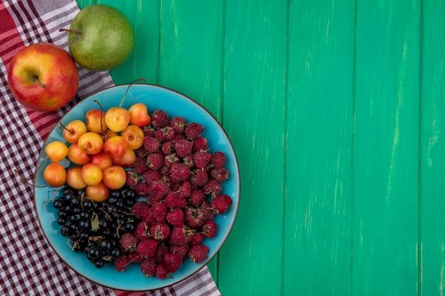 Vista superior de maçãs coloridas com framboesas, cerejas brancas e groselhas pretas em um prato sobre uma superfície verde