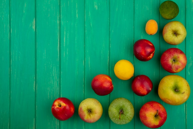Vista superior de maçãs coloridas com pêssegos e limão com limão em uma superfície verde