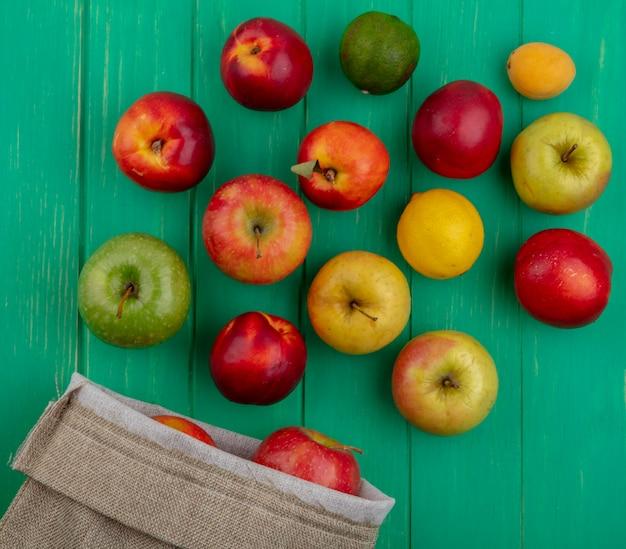 Vista superior de maçãs coloridas com pêssegos, limão e lima em um saco de estopa sobre uma superfície verde