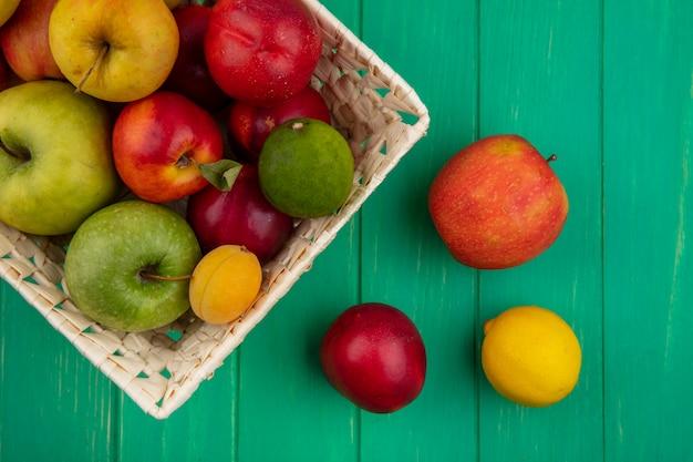 Vista superior de maçãs coloridas com pêssegos, limão e lima em uma cesta em uma superfície verde