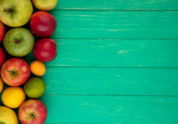 Vista superior de maçãs coloridas com pêssegos, limão e lima em uma superfície verde