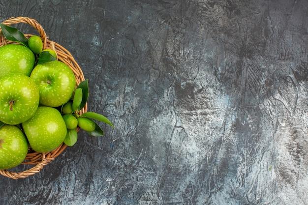 Vista superior de maçãs da cesta de madeira das apetitosas maçãs verdes com folhas