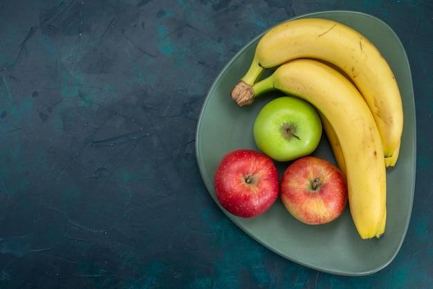Vista superior de maçãs frescas com bananas em uma mesa azul-escura