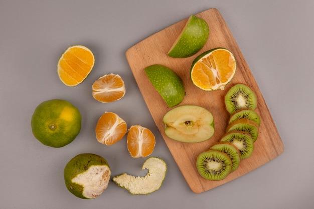 Vista superior de maçãs frescas com fatias de kiwi em uma placa de cozinha de madeira com tangerinas isoladas
