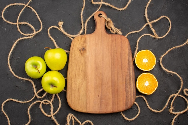 Vista superior de maçãs frescas com limão em fundo escuro.