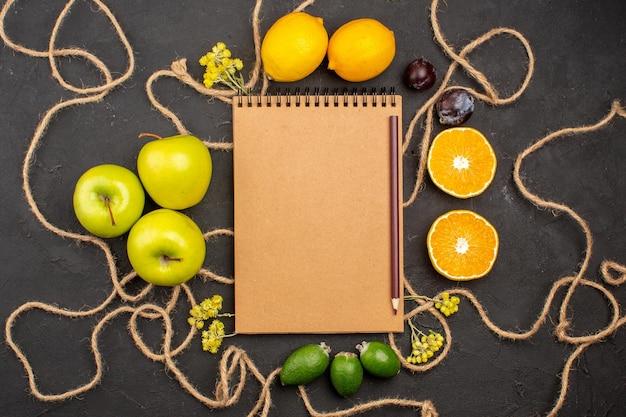 Vista superior de maçãs frescas com limões em fundo escuro frutas cítricas frescas